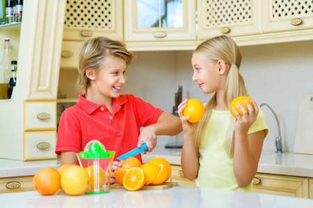 Funny teenagers with citrus. Boy and girl holding fruit oranges