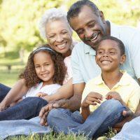 African American Grandparents With Grandchildren Relaxing In Par